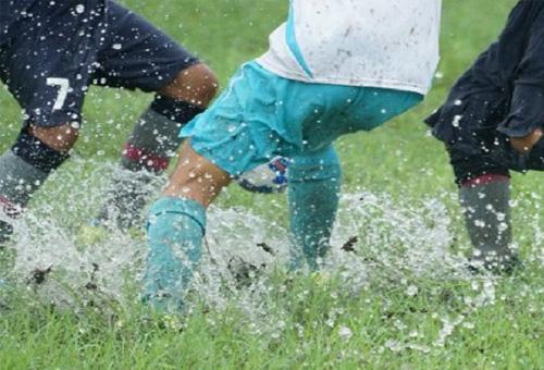 photo de match de foot sur terrain quasiment inondé (énormes éclaboussures d'eau)