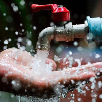photo d'une main récupérant l'eau s'écoulant d'un robinet d'eau, en extérieur